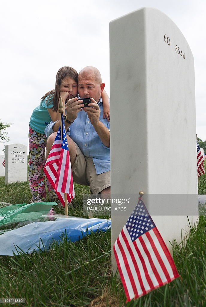 Arlington, Virginia, resident David Presson takes his daughter Abigail, 8, on a 'history & life' lesson and visit Arlington National Cemetery May 28, 2010, placing flowers at the gravesite of US Army Pfc. Ross A. McGinnis, whom they have no direct connection with, and who earned the Silver Star Medal for taking the force of a grenade explosion to save his fellow soldiers in Baghdad on December 4, 2006. Presson and his daughter researched heroic US soldiers and is reading the entire record of McGinnis's heroism, from his Iphone. They visited several heroic fallen soldiers gravesites as part of his Memorial Day 'history & life' lessons with his daughter. AFP Photo/Paul J. Richards