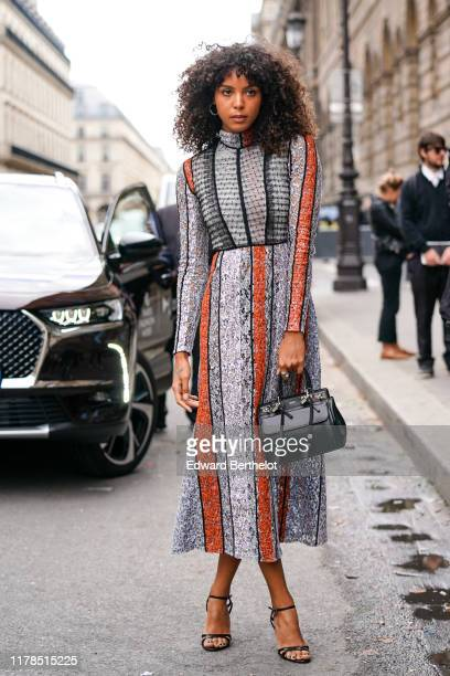 Arlissa Ruppert wears earrings a hineck long sleeves grey white and orange lace dress black heeled sandals a black Giambattista Valli handbag outside...