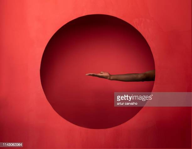 arm and hand on set red background - circle stock pictures, royalty-free photos & images