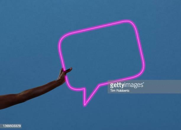 arm holding neon light speech bubble - human body part stock pictures, royalty-free photos & images