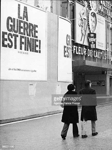 Arm in arm a couple walk past posters that read 'La Guerre est Finie Si Vous le Voulez John et Yoko Lennon vous souhaitent un Joyeux Noel' on the...