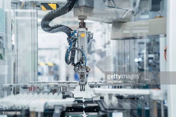 arm of assembly robot functioning inside modern factory, stuttgart, germany - industriebetrieb stock-fotos und bilder