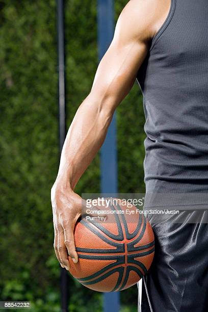 arm of man holding baskeball against his thigh