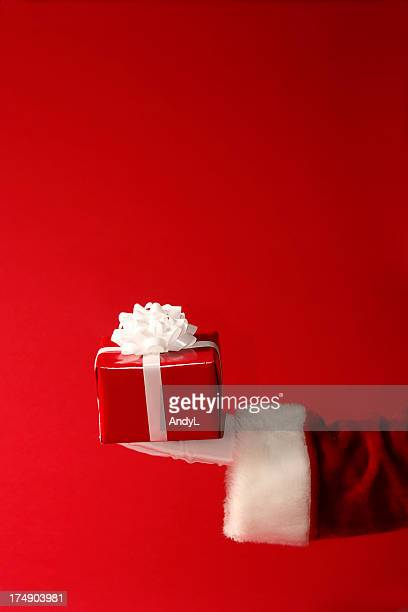 Arm of Santa Claus holding out a red and white present