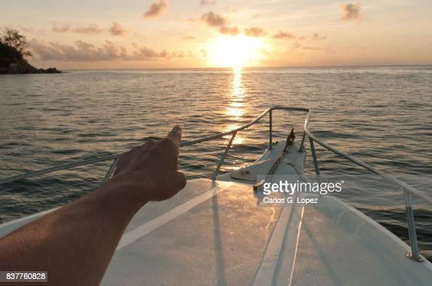 arm pointing at sunset on white boat at sunset - schiffsbug stock-fotos und bilder