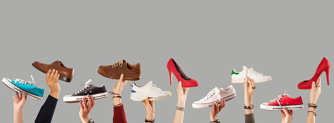 arm raised and holding shoes 1090643210