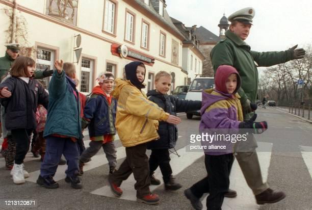 Arm raus, schauen, losgehen: Polizeikommissar Stefan Löseke führt am 27.1.2000 eine Gruppe von Schulkindern der Mainzer Eisgrubschule über einen...