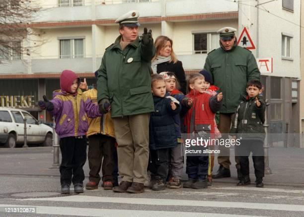 Arm raus, schauen, losgehen: Polizeikommissar Stefan Löseke und sein Kollege Hans Joachim Schneisz führt am 27.1.2000 eine Gruppe von Schulkindern...