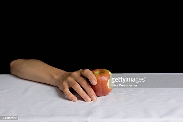 Arm resting on table and holding apple