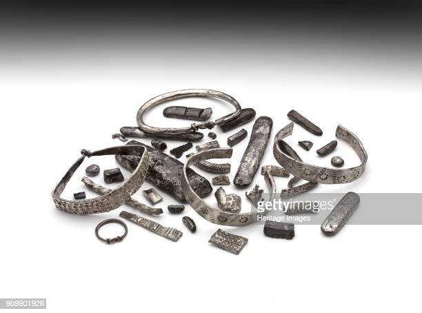 Arm ring, 910. Part of hoard consisting of: penannular arm rings; hammered silver ribbon; zig-zag ornament, rows of punched holes; between circles of...
