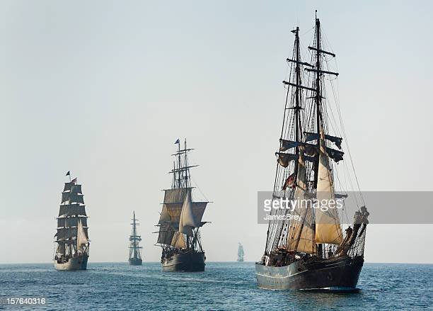 armada of tall ships sails at morning - pirate ship stock photos and pictures