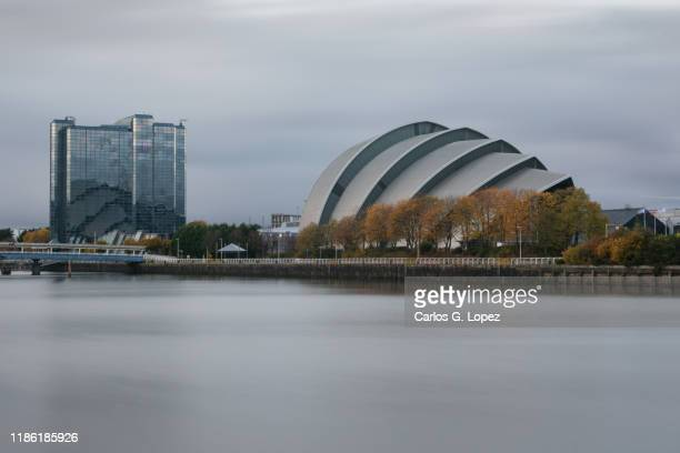 sec armadillo auditorium and modern high-rise building under an overcast sky near the river clyde in glasgow, scotland, united kingdom - clyde auditorium stock pictures, royalty-free photos & images