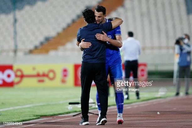 Arman Ramezani of Esteghlal hugs his head coach during the Persian Gulf Pro League match between Esteghlal and Padideh FC at Azadi Stadium on June...