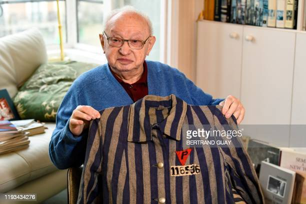 Armand Bulwa survivor of the Buchenwald concentration camp poses with a Polish political prisoner uniform during a photo session in Paris on January...