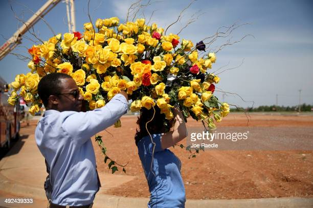 Armand McCoy and Jennifer Halstead carry a boquet of flowers past empty land where the Moore Medical Center used to stand during the remembrance...