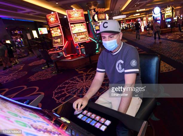Armando Alvarado of Illinois wears a mask as he plays a slot machine at Mandalay Bay Resort and Casino after the Las Vegas Strip property opened for...