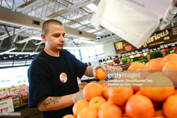 Armando Arias stocks oranges in the produce section Tuesday Aug 13 at the new Lucky's Market in Longmont