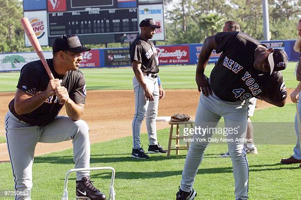Armando Benitez studies the angles as teammate Rey Ordonez tries out an unusal batting stance on picturetaking day at the New York Mets spring...