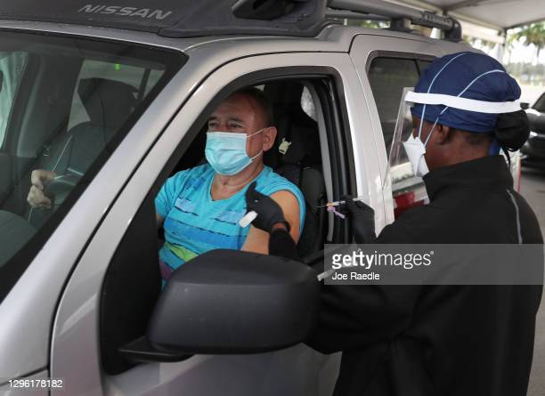 Armando Bravo receives a COVID-19 vaccine from a healthcare worker at a drive-thru site at Tropical Park on January 13, 2021 in Miami, Florida....