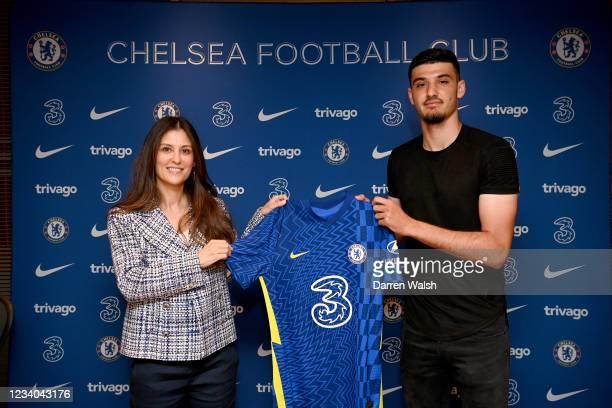Armando Broja of Chelsea signs a contract extension alongside Chelsea director Marina Granovskaia at Stamford Bridge on July 18, 2021 in London,...