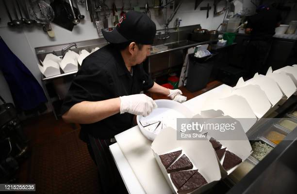 Armando Castro the pantry chef at Sociale puts chocolate cake in togo boxes on March 27 2020 in San Francisco California Sociale is working with a...