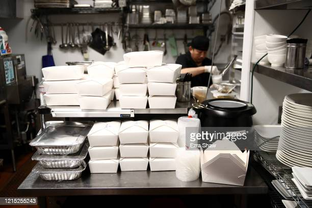 Armando Castro the pantry chef at Sociale puts chocolate cake in togo boxes behind boxes of salads ready for delivery on March 27 2020 in San...
