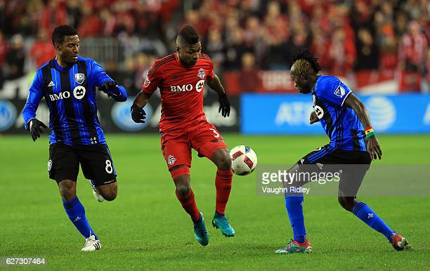 Armando Cooper of Toronto FC battles for the ball with Patrice Bernier and Dominic Oduro of Montreal Impact during the first half of the MLS Eastern...