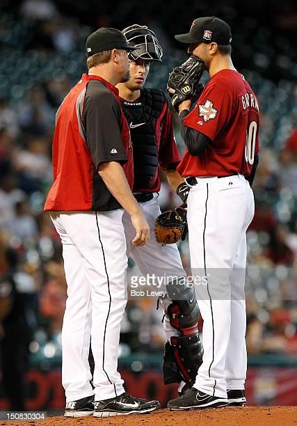 Armando Galarraga of the Houston Astros talks with pitching coach Doug Brocail of the Houston Astros and catcher Jason Castro of the Houston Astros...