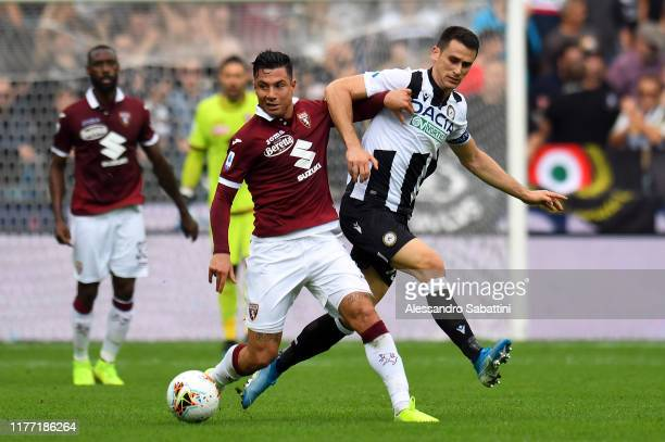 Armando Izzo of Torino FC competes for the ball with Kevin Lasagna of Udinese Calcio during the Serie A match between Udinese Calcio and Torino FC at...