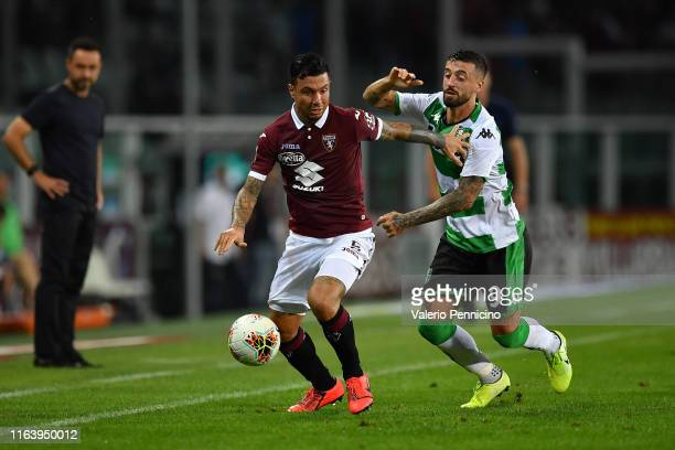 Armando Izzo of Torino FC is challenged by Francesco Caputo of US Sassuolo during the Serie A match between Torino FC and US Sassuolo at Stadio...