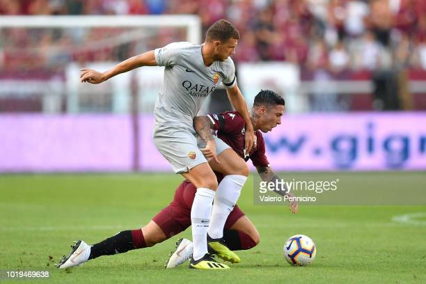 Armando Izzo of Torino FC is tackled by Edin Dzeko of AS Roma during the Serie A match between Torino FC and AS Roma at Stadio Olimpico di Torino on...