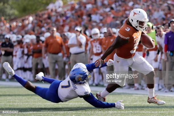 Armanti Foreman of the Texas Longhorns gets past the tackle attempt by David Williams of the San Jose State Spartans in the fourth quarter at Darrell...