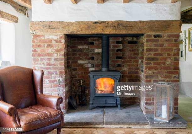 armchair and fireplace in living room - cooker stock pictures, royalty-free photos & images