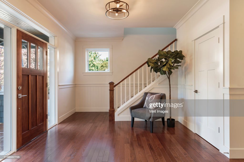 Armchair and tree in house entryway : Stock Photo