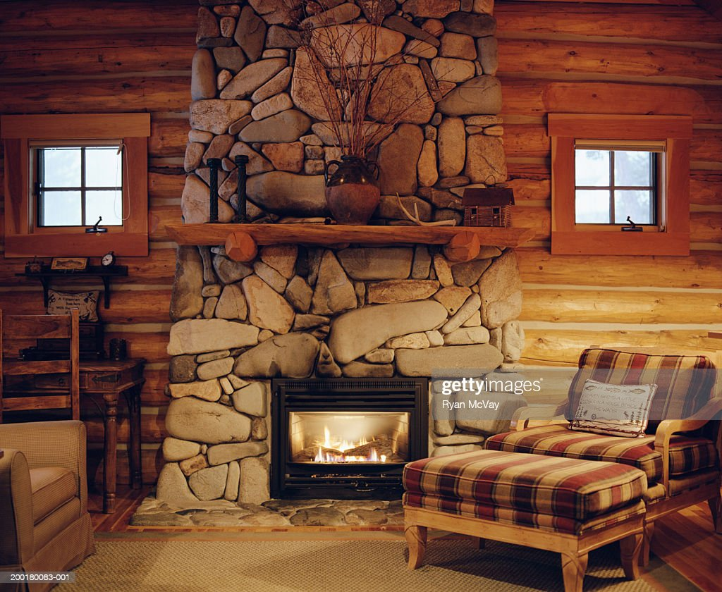 Armchair beside stone fireplace in log cabin stock photo for Cabin fireplace pictures
