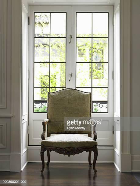 Armchair beside windows in living room