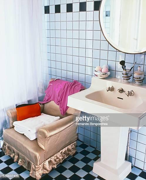Armchair by Pedestal Sink in Tiled Bathroom