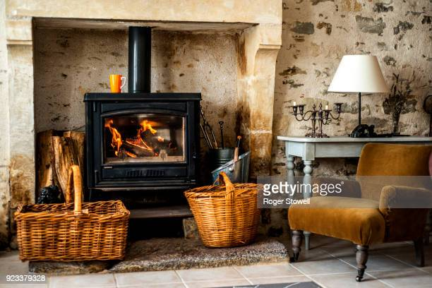 armchair by the fire in country house. - wood burning stove stock photos and pictures