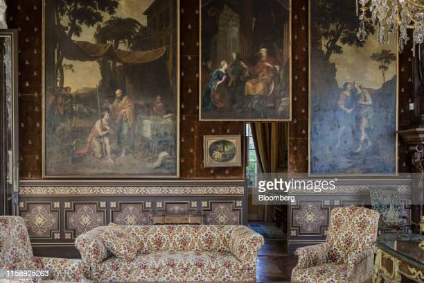 Armchairs and sofa sit beside 19th century portraits adorning the walls of a sitting room inside the Villa Les Cedres a 187yearold000squarefoot...