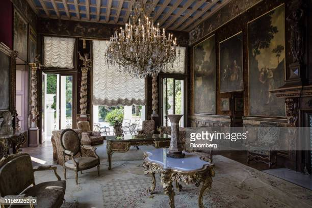 Armchairs and tables stand beneath chandeliers as 19th century portraits adorn the walls of a sitting room inside the Villa Les Cedres a...