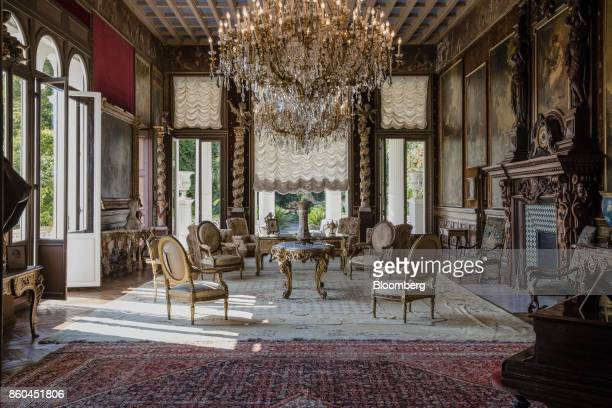 Armchairs and tables stand beneath chandeliers as 19th century portraits in ornate frames adorn the walls of a sitting room inside the Villa Les...