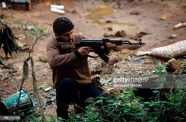 Armed and kneeling guerrilla fighter aiming a light machinegun Italian US and French troops recently left the Lebanese territory after the...