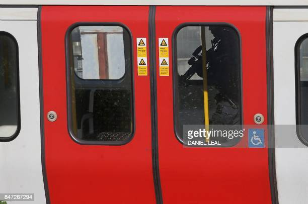 A armed British police officer walks through the carriage of a London underground tube carriage at Parsons Green underground tube station in west...