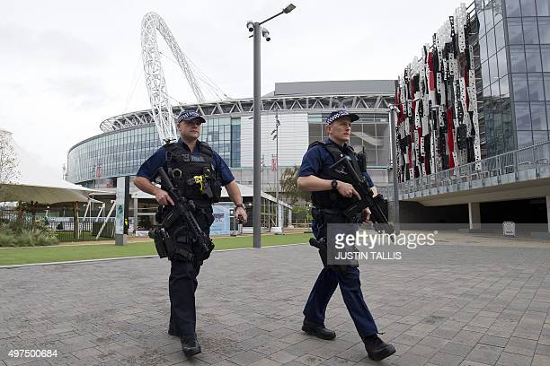 Armed British police officers patrol around Wembley Stadium in west London on November 17 ahead of the international friendly football match between...