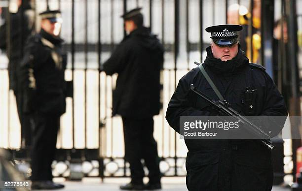 Armed British police officers patrol inside Downing Street after a cabinet meeting on March 3 2005 in London England The House of Lords is beginning...