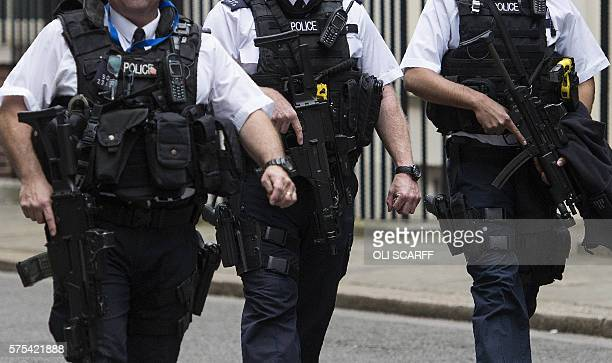 Armed British police officers patrol near 10 Downing Street the official residence of British Prime Minister Theresa May in central London on July 15...