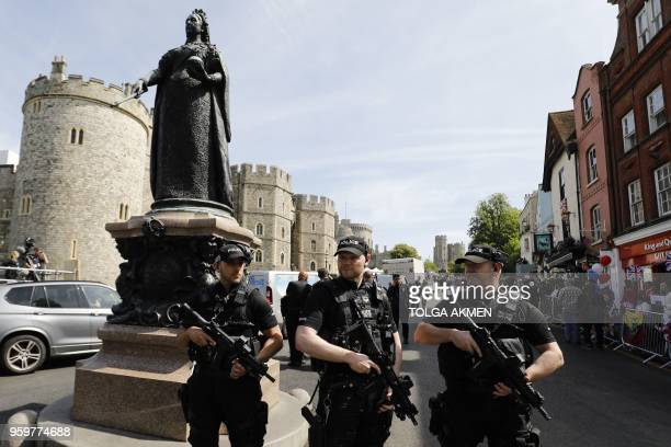 Armed British police officers patrol near Windsor Castle in Windsor on May 18 the day before the Royal wedding Britain's Prince Harry and US actress...