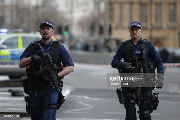 Armed British police officers patrol outside the Houses of Parliament in Westminster central London on March 22 2017 during an emergency incident...