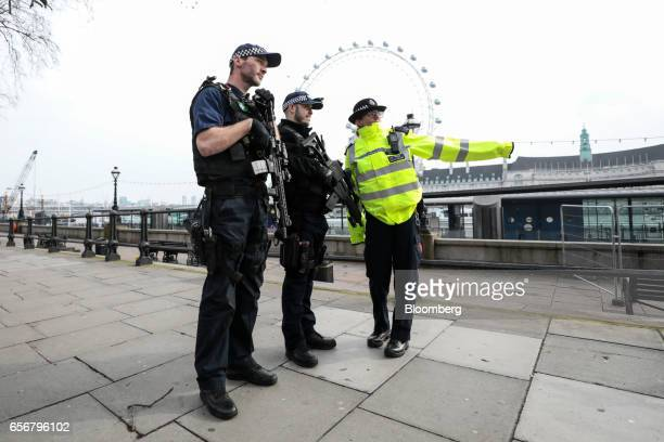 Armed British police officers speak with a colleague in the Westminster district of central London UK on Thursday March 23 2017 Parliament will...