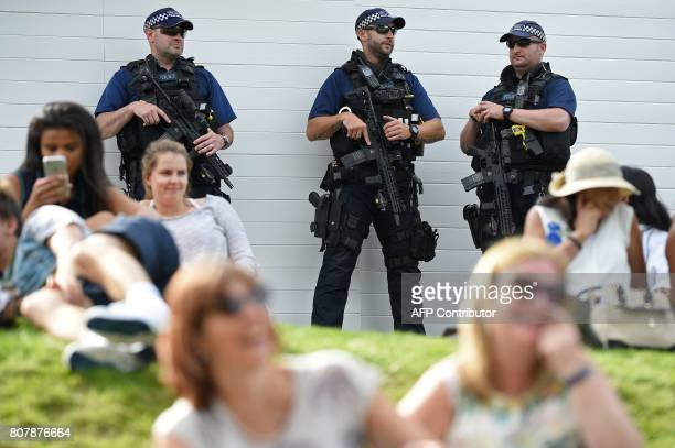 Armed British police officers stand on duty at The All England Lawn Tennis Club in Wimbledon southwest London on July 4 2017 on the second day of the...